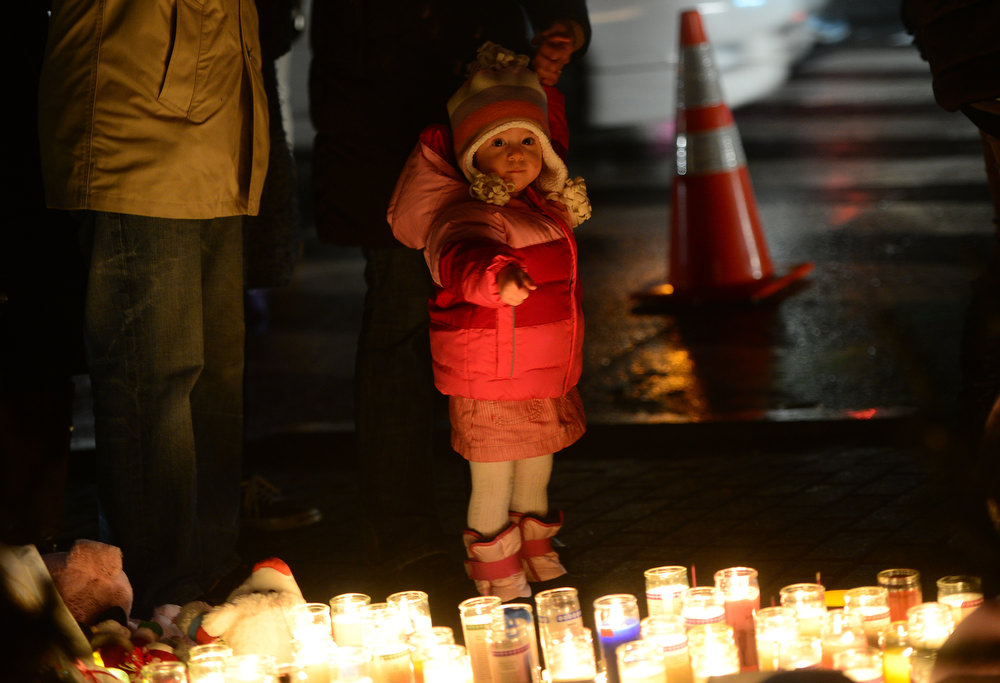 Description of . A young child points at candles as people pay their respects at a makeshift shrine to the victims of a elementary school shooting in Newtown, Connecticut, December 16, 2012.  A young gunman slaughtered 20 small children and six teachers on December 14, 2012 after walking into a school in an idyllic Connecticut town wielding at least two sophisticated firearms. AFP PHOTO/Emmanuel DUNAND/AFP/Getty Images