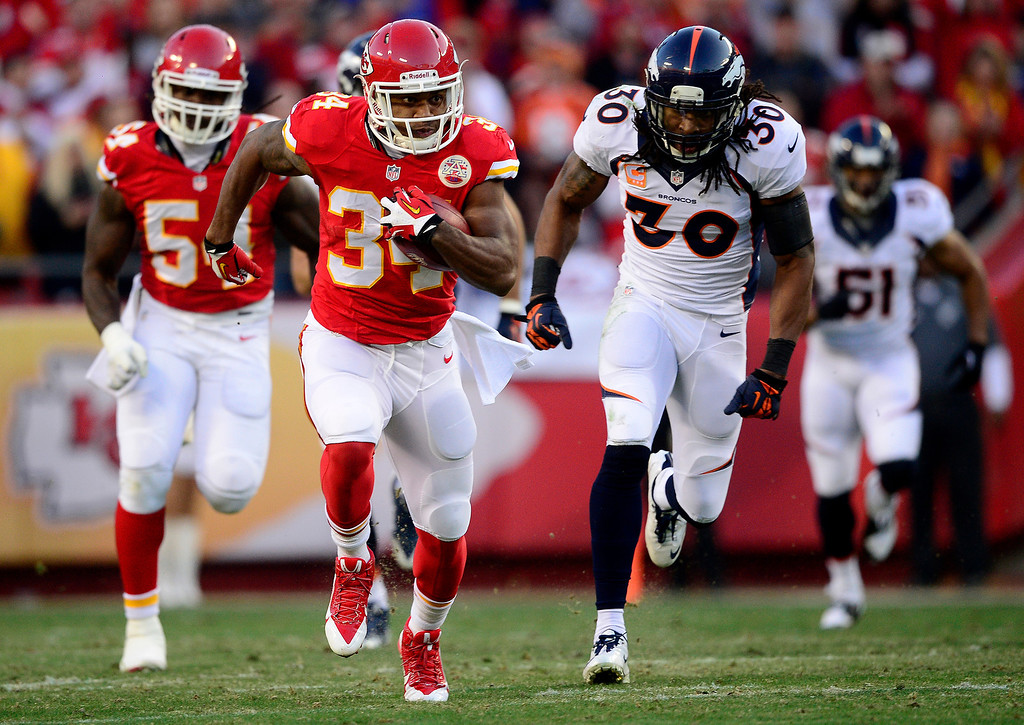 . Knile Davis (34) of the Kansas City Chiefs runs a kick back for a touchdown as David Bruton (30) of the Denver Broncos pursues during the first half of the Broncos\' 35-28 win at Arrowhead Stadium. (Photo by AAron Ontiveroz/The Denver Post)