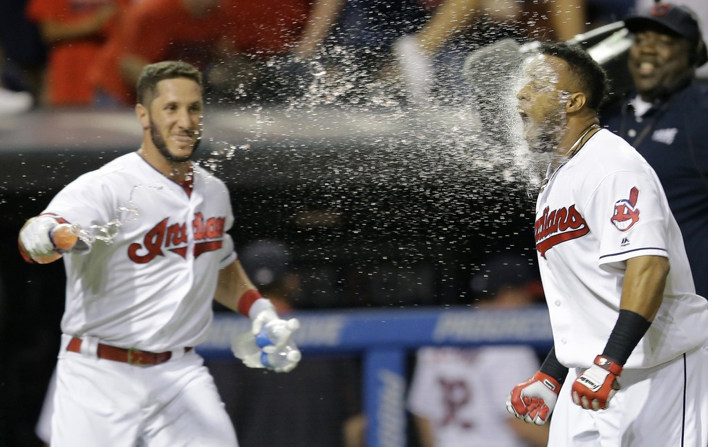 . Cleveland Indians\' Yan Gomes, left, throws water at Carlos Santana after Santana hit the game-winning solo home run off Chicago White Sox relief pitcher Nate Jones during the ninth inning of a baseball game, Friday, June 17, 2016, in Cleveland. The Indians won 3-2. (AP Photo/Tony Dejak)