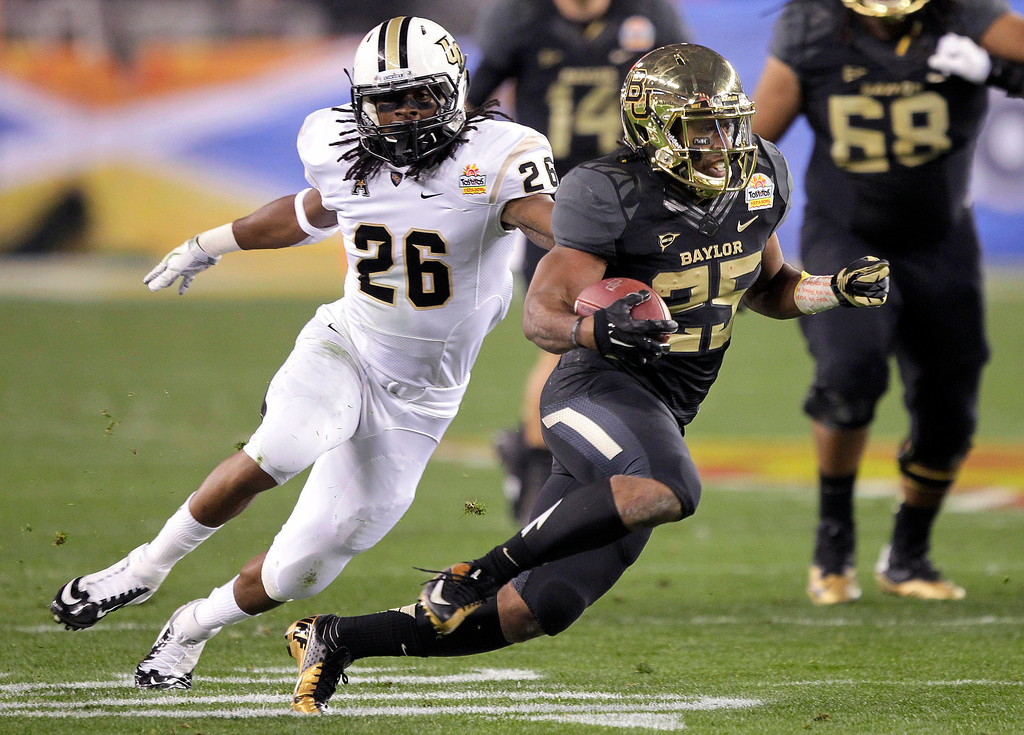 . Baylor running back Lache Seastrunk (25) runs for a first down as Central Florida defensive back Clayton Geathers (26) pursues during the first half of the Fiesta Bowl NCAA college football game, Wednesday, Jan. 1, 2014, in Glendale, Ariz. (AP Photo/Rick Scuteri)