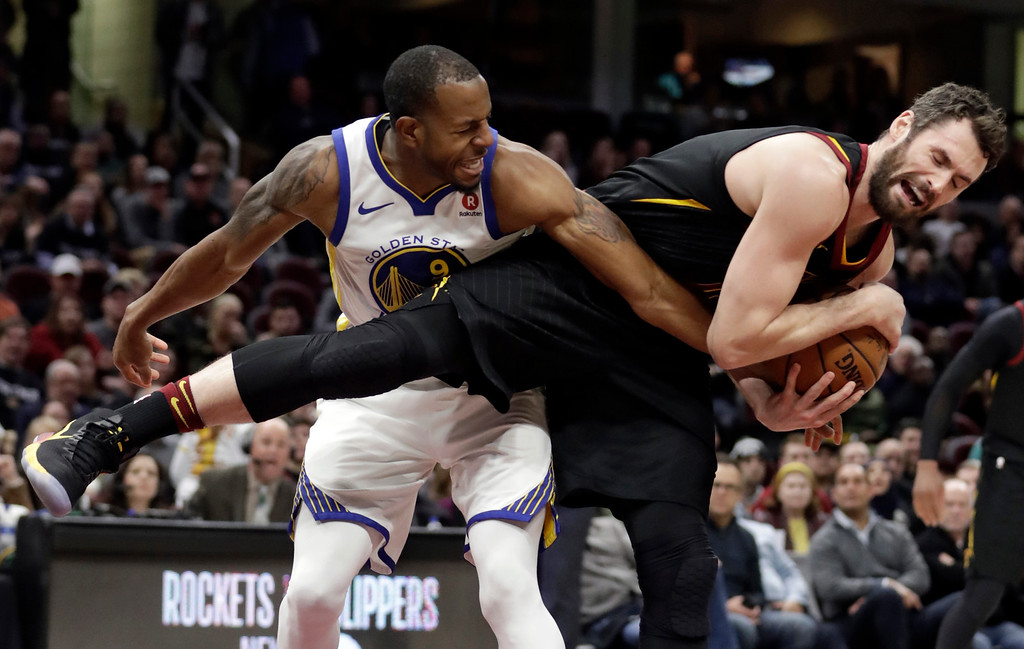 . Cleveland Cavaliers\' Kevin Love, right, grabs a rebound ahead of Golden State Warriors\' Andre Iguodala in the second half of an NBA basketball game, Monday, Jan. 15, 2018, in Cleveland. (AP Photo/Tony Dejak)