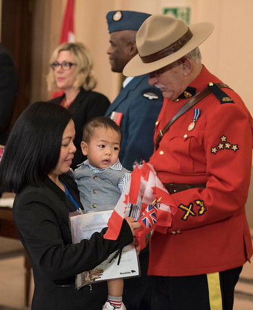 Ednalene Magnayi and her 9-month-old son Andry receive Canadian flags during a citizenship ceremony after the family became Canadian Citizens at the Manitoba Legislative Building Wednesday February 1, 2017. His family are originally from the Philippines. (David Lipnowski for Metro News)