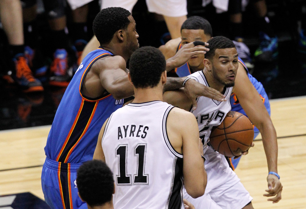 . Cory Joseph #5 of the San Antonio Spurs with the ball against Perry Jones #3 of the Oklahoma City Thunder in the second half in Game One of the Western Conference Finals during the 2014 NBA Playoffs at AT&T Center on May 19, 2014 in San Antonio, Texas.  (Photo by Chris Covatta/Getty Images)