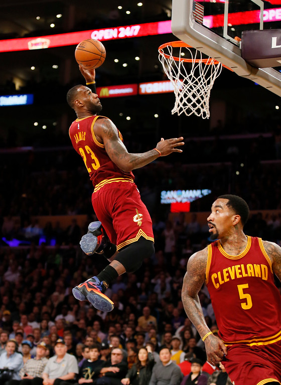 . Cleveland Cavaliers\' LeBron James, left, prepares to dunk after teammate J.R. Smith, right, passed the ball to him by bouncing it off the backboard, during the first half against the Los Angeles Lakers in an NBA basketball game, Thursday, March 10, 2016, in Los Angeles. (AP Photo/Danny Moloshok)