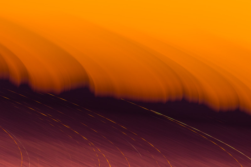 Abstract sweeping oranges and dash lights of a city below in airplane