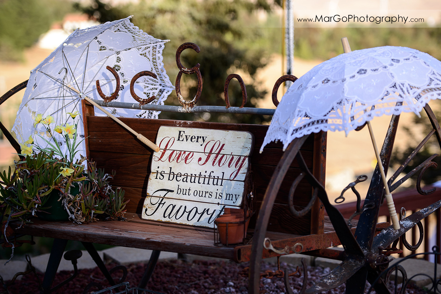 wedding ceemony decor made of wooden sign and two white umbrellas