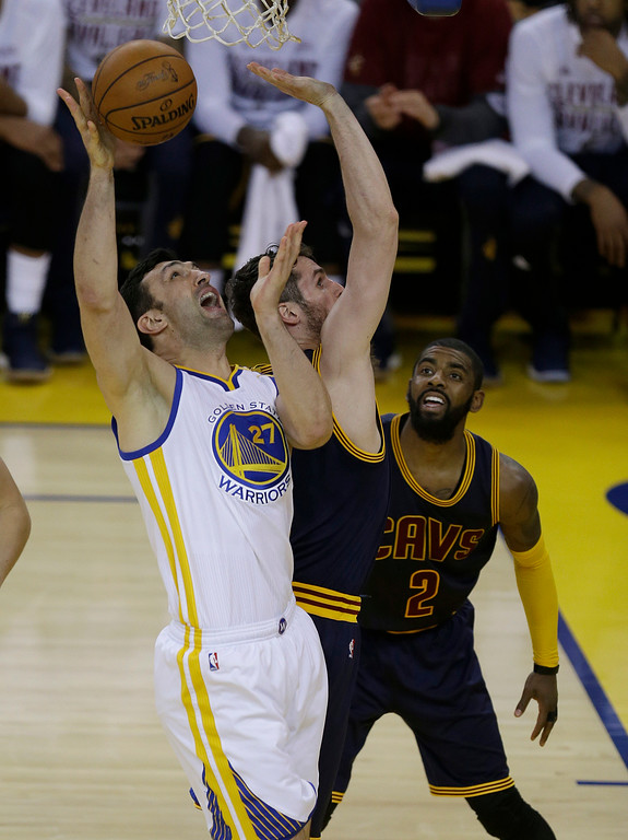 . Golden State Warriors center Zaza Pachulia (27) shoots against Cleveland Cavaliers forward Kevin Love, center, and guard Kyrie Irving (2) during the second half of Game 1 of basketball\'s NBA Finals in Oakland, Calif., Thursday, June 1, 2017. (AP Photo/Ben Margot)