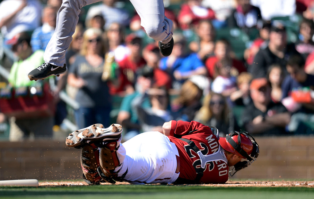 . SCOTTSDALE, AZ. - FEBRUARY 23: Dexter Fowler (24) of the Colorado Rockies flies over Miguel Montero (26) of the Arizona Diamondbacks to score in the fourth inning February 23, 2013 in Scottsdale. (Photo By John Leyba/The Denver Post)