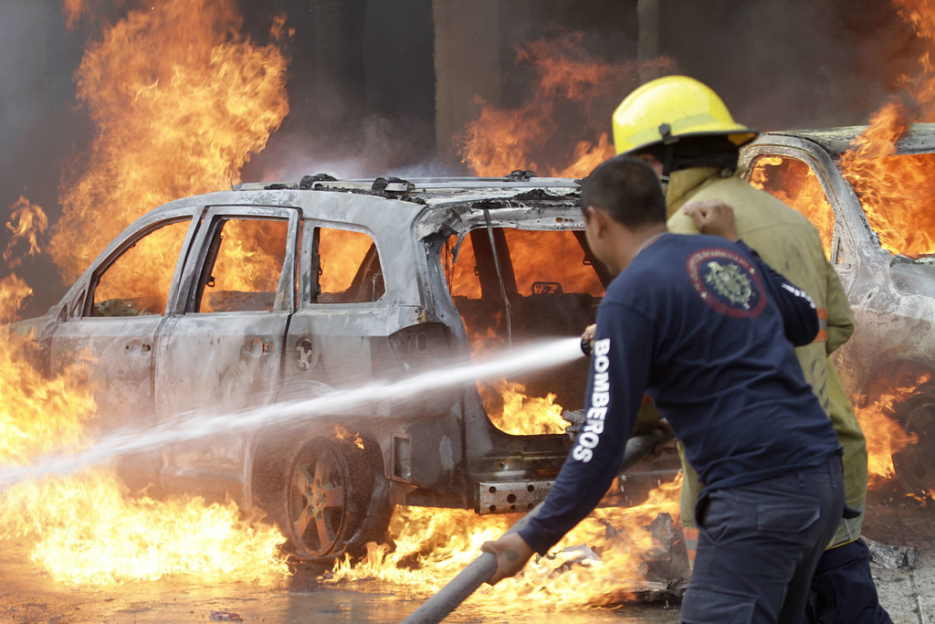 . Firefighters try to extinguish the fire on vehicles set ablaze by protesters in Chilpancingo, Guerrero State, Mexico on November 12, 2014. Pedro PARDO/AFP/Getty Images