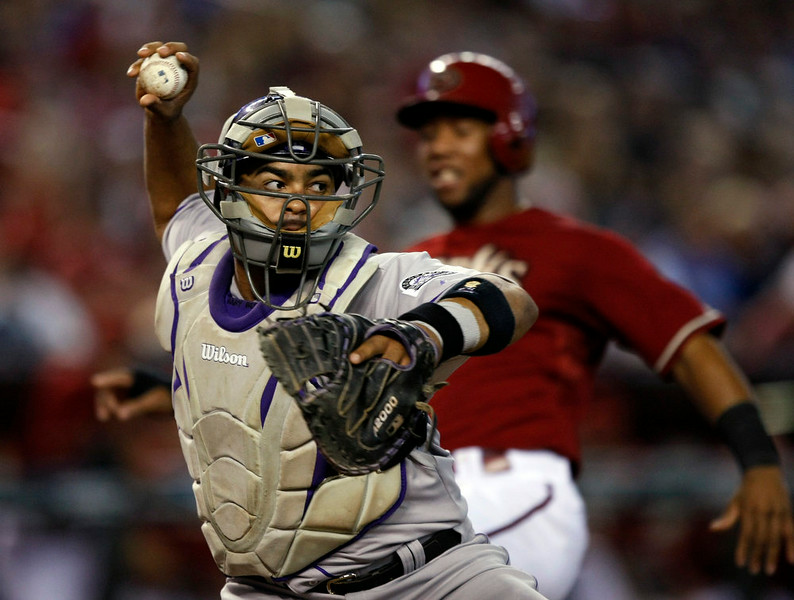 . Colorado Rockies catcher Wilin Rosario (20) gets the force out and then commits an throwing error in the fourth inning during a baseball game  against the Arizona Diamondbacks Sunday, Aug. 10, 2014, in Phoenix. (AP Photo/Rick Scuteri)