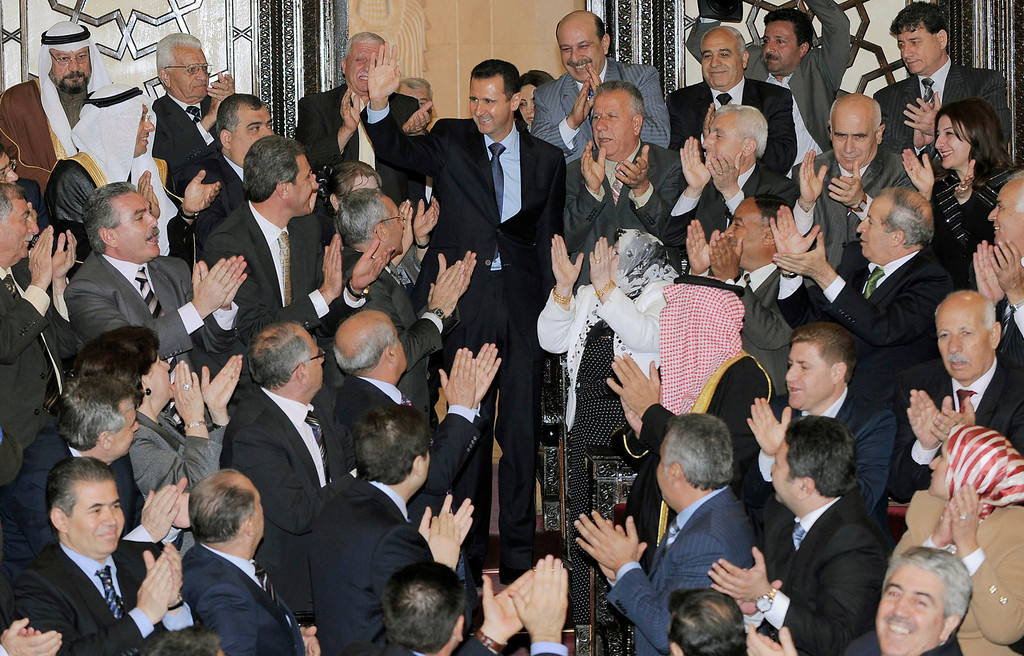 . FILE - In this photo provided by the Syrian official news agency SANA, Syrian President Bashar Assad, center top, greets lawmakers before his speech at the Parliament in Damascus, Syria, Wednesday, March 30, 2011. (AP Photo/SANA, File)