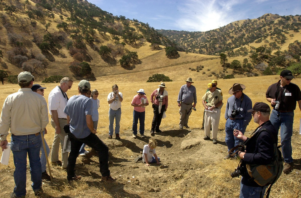 . Participants crowd around as they try to determine whether this part of a home was a bathroom or a kitchen by examining remnants of an old pipe during the Tesla and Pottery Site Tour in the Jimtown area of Tesla led by historian Dan Mosier on Sept. 7, 2003, in Livermore, Calif. (Susan Tripp Pollard/Staff Archives)