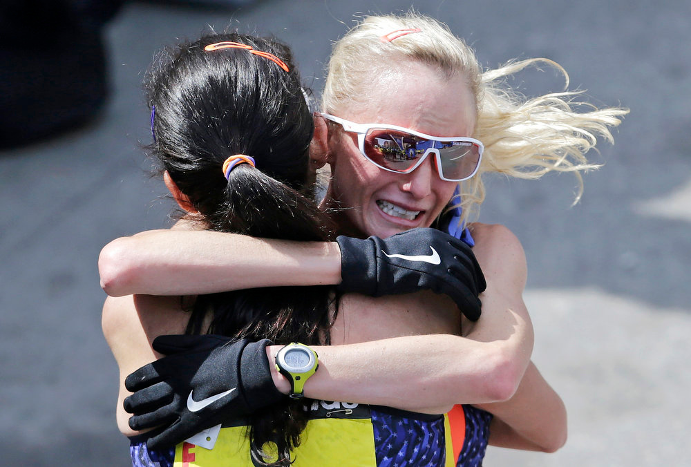 . Shalane Flanagan, right, is embraced by Kara Goucher, both of the United States, after finishing the 2013 running of the Boston Marathon in Boston, Monday, April 15, 2013. Flanagan finished fourth and Goucher sixth in the women\'s division of the race. (AP Photo/Charles Krupa)