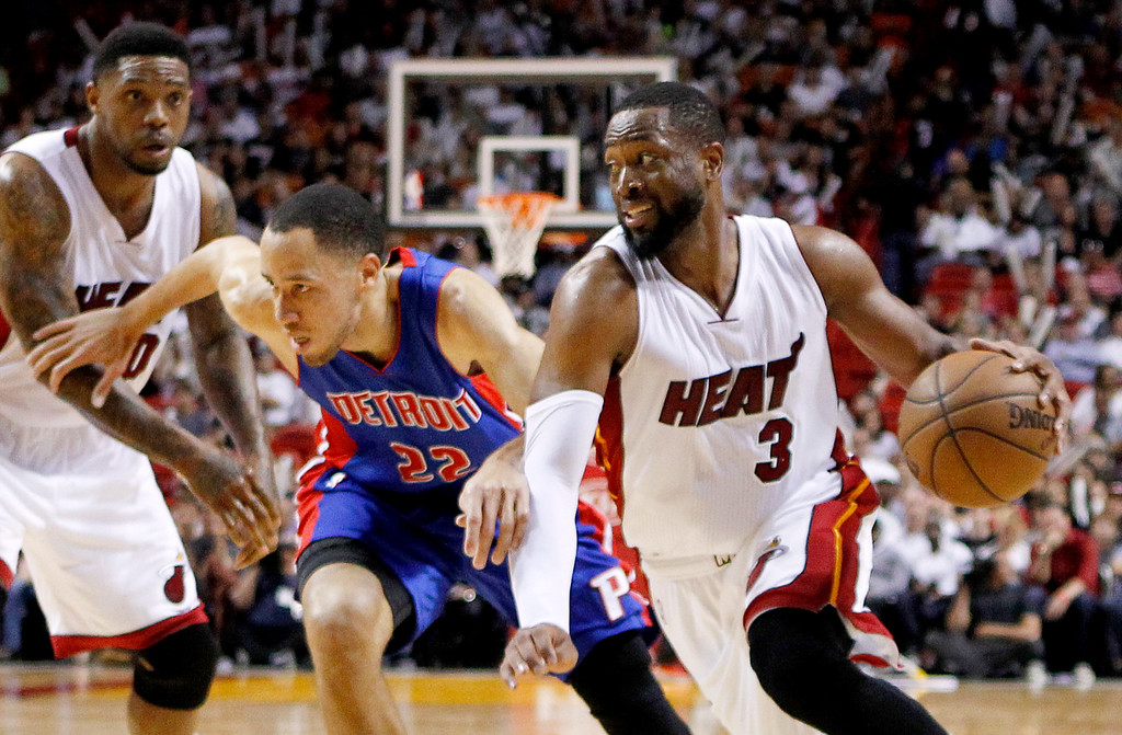 . Miami Heat guard Dwyane Wade (3) drives to the basket ahead of Detroit Pistons forward Tayshaun Prince during the second half of an NBA basketball game, Sunday, March 29, 2015, in Miami. At left is Miami Heat forward Udonis Haslem. (AP Photo/Joe Skipper)