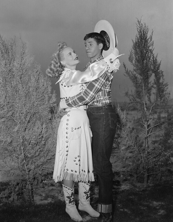 . In a spot most men would envy, Jerry Lewis appears quite at a loss in the face of amorous advances on the part of actress Marie Wilson during filming on location on April 11, 1950 at Las Vegas, Nev.   (AP Photo)