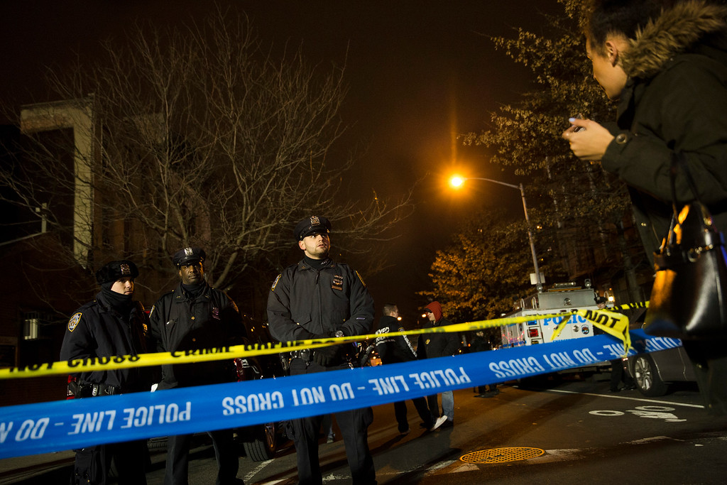 . Police guard the scene where two NYPD officers were shot, Saturday, Dec. 20, 2014, in New York.  An armed man walked up to two New York Police Department officers sitting inside a patrol car and opened fire Saturday afternoon, killing one and critically wounding a second before running into a nearby subway station and committing suicide, police said. (AP Photo/John Minchillo)
