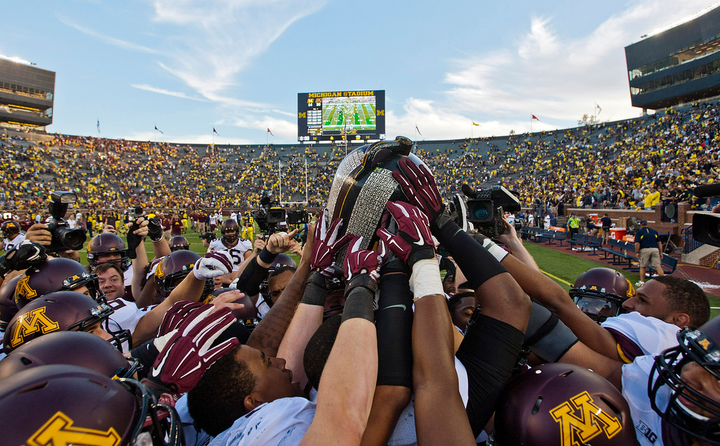 . Minnesota players lift up the Little Brown Jug trophy after an NCAA college football game against Michigan in Ann Arbor, Mich., Saturday, Sept. 27, 2014. Minnesota won 30-14. (AP Photo/Tony Ding)