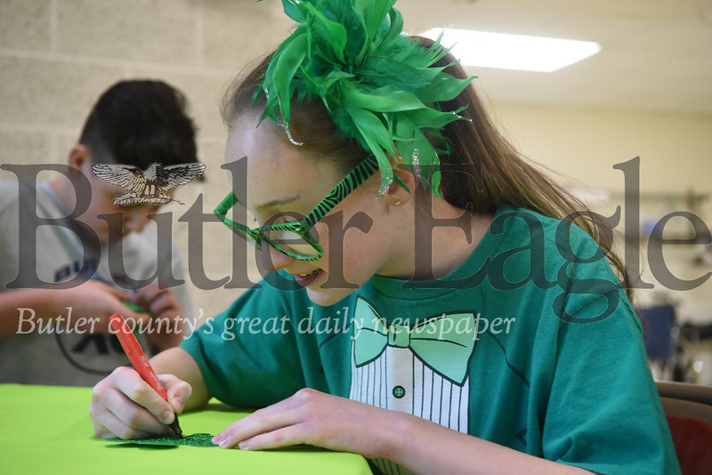 Moniteau Junior and Senior High School seventh-grader Jaycee Relihan, 13, writes her name on a shamrock nameplate during St. Patrick Game Night on Sunday at Christ Community United Methodist Church.