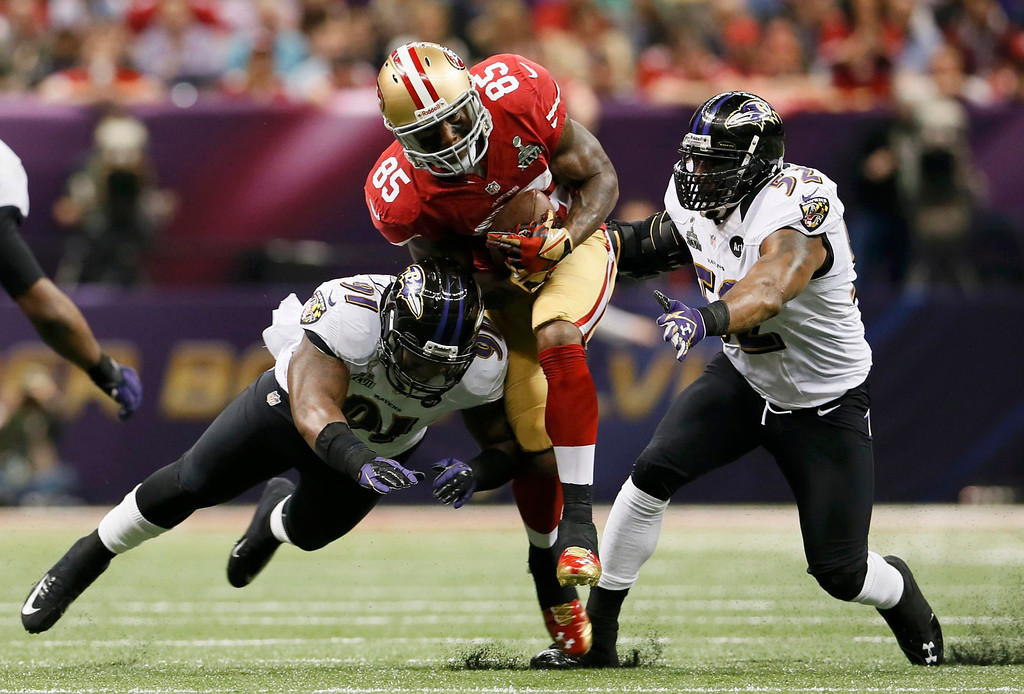 . San Francisco 49ers tight end Vernon Davis (85) is tackled by Baltimore Ravens inside linebacker Ray Lewis (52) and outside linebacker Courtney Upshaw (91) during the second quarter in the NFL Super Bowl XLVII football game in New Orleans, Louisiana, February 3, 2013. REUTERS/Lucy Nicholson