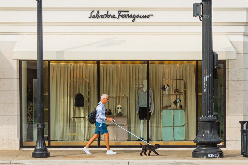 A man walks his dog past the Salvatore Ferragamo store front at the intersection of Worth Avenue and S. County Road in Palm Beach, Friday, April 24, 2020. Stores on Worth Avenue have been closed due to the coronavirus pandemic. [JOSEPH FORZANO/palmbeachdailynews.com]