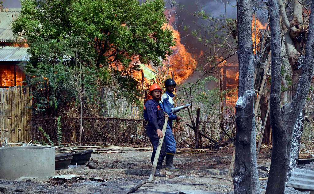 . Myanmar fire fighters put out fires in a burning building following ethnic unrest between Buddhists and Muslims in Meikhtila, Mandalay division, about 550 kilometers (340 miles) north of Yangon, Myanmar, Friday, March 22, 2013. (AP Photo/Khin Maung Win)