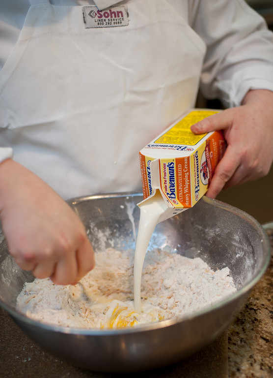 . Emma Currie adds heavy whipping cream to ingredients for bacon, cheddar & chive scones. (Sun photo by Holly Mahaffey/@hollymahaffey)