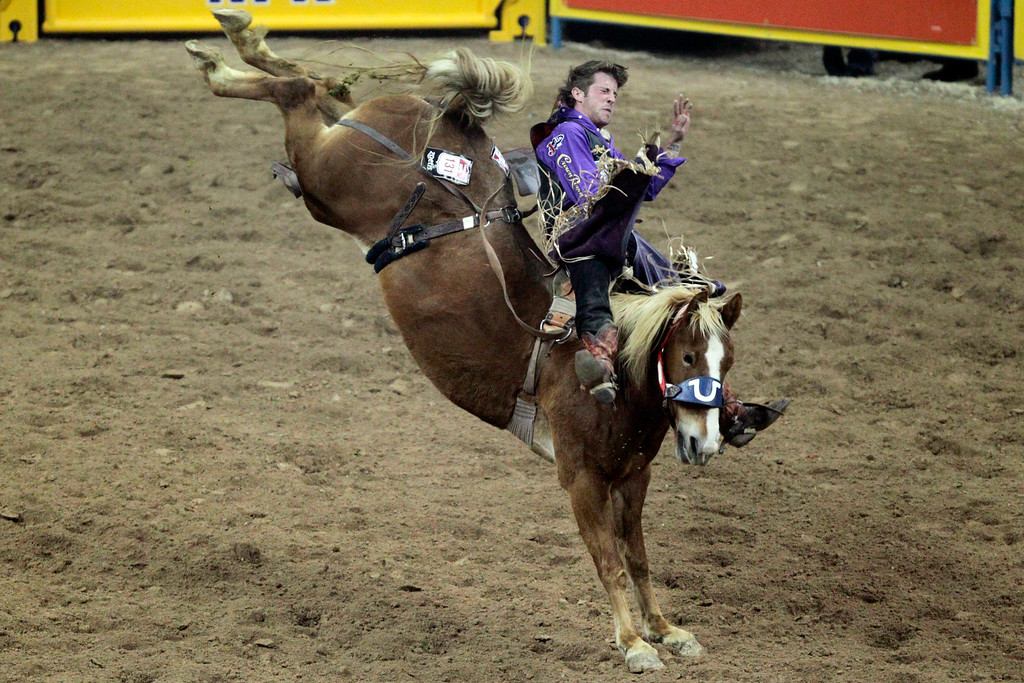 . Tilden Hooper competes in bareback riding during the fourth round at the National Finals Rodeo at the Thomas & Mack Center in Las Vegas on Sunday, Dec. 7, 2014. (AP Photo/Las Vegas Review-Journal, Erik Verduzco)