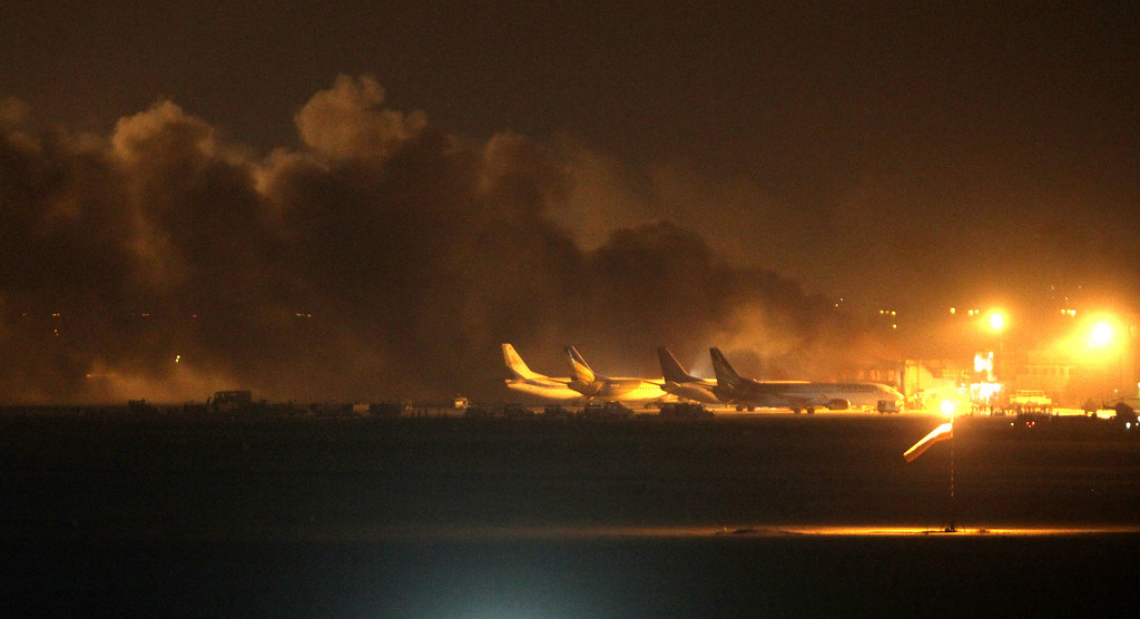 . Fire illuminates the sky above the Jinnah International Airport in Karachi where security forces are fighting with attackers Sunday night, June 8, 2014, in Pakistan. Gunmen disguised as police guards attacked a terminal with machine guns and a rocket launcher during a five-hour siege that killed a number of people as explosions echoed into the night, while security forces retaliated and killed all the attackers, officials said Monday. (AP Photo/Fareed Khan)