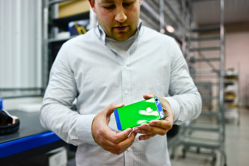 . Jason Sobotta, ColorWare vice president of business development, holds a finished iPhone waiting to be shipped. (Pioneer Press: Simon Guerra)