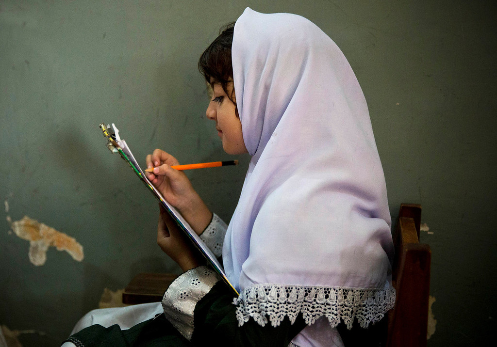 . A young Pakistani girl works on her mid-term papers in a school in Mingora, Swat Valley, Pakistan on Saturday, Oct 5, 2013. One year after a Taliban bullet tried to silence Malala Yousufzai\'s demand for education, she has published a book and is a contender for the Nobel Peace Prize. But still the militants threaten to kill her should she dare return home to Pakistan, and the principal at her old school says that as Malala\'s fame has grown, so has fear in her classrooms. (AP Photo/Anja Niedringhaus)