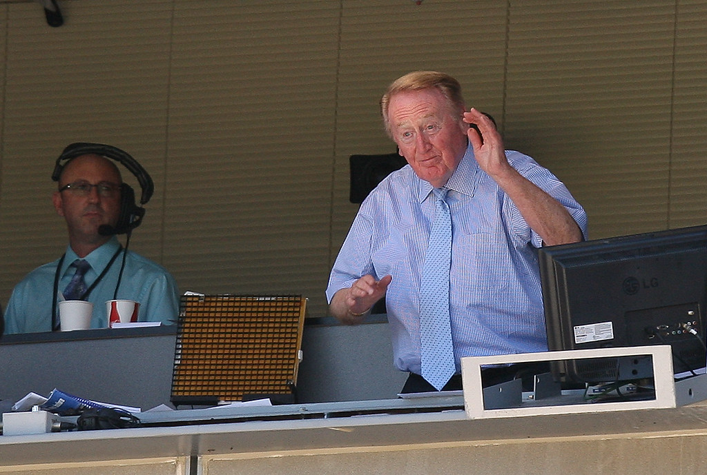. Hall of Fame broadcaster Vin Scully waves to the crowd in the middle of the third inning as he announced that he will return for a 62nd season with the Los Angeles Dodgers broadcast both home and western division games before a Major League baseball game between the Cincinnati Reds and the Los Angeles Dodgers at Dodger Stadium on Sunday, August 22, 2010, in Los Angeles. (SGVN/Staff Photo by Keith Birmingham/SPORTS)