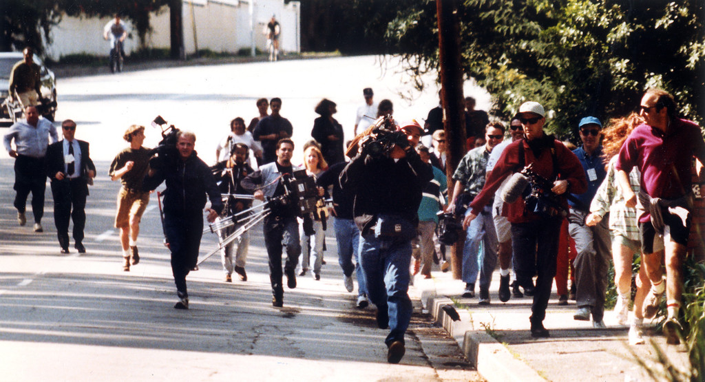 . Members of the media sprint along Sunset Blvd after realizing they had set up their equipment on the wrong corner to get pictures of the Simpson trial motorcade.   (2/12/95)   (Los Angeles Daily News file photo)