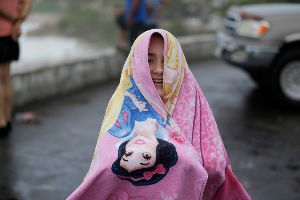 . A girl covers herself with a towel as rain falls in Los Cabos, Mexico,  Sunday, Sept. 14, 2014. Hurricane Odile grew into a major storm Sunday and took aim at the resort area of Los Cabos, prompting Mexican authorities to evacuate vulnerable coastal areas and prepare shelters for up to 30,000 people. (AP Photo/Victor R. Caivano)