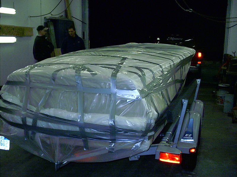 Boat wrapped in plastic leaving for finish shop.