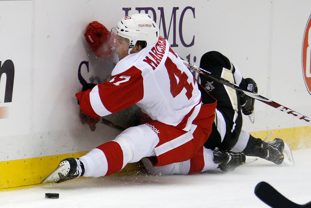 . Detroit Red Wings\' Alexei Marchenko (47) slams in to the boards on top of Pittsburgh Penguins\' Bobby Farnham during the second  period of a NHL pre-season hockey game in Pittsburgh Monday, Sept. 22, 2014.Both players remained in the game. (AP Photo/Gene J. Puskar)