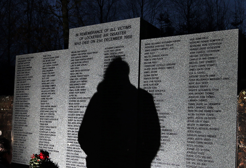 . The shadow of a member of the public is seen looking at the main memorial stone in memory of the victims of Pan Am flight 103 bombing, in the garden of remembrance at Dryfesdale Cemetery, near Lockerbie, Scotland. Saturday Dec. 21, 2013.  (AP Photo/Scott Heppell).