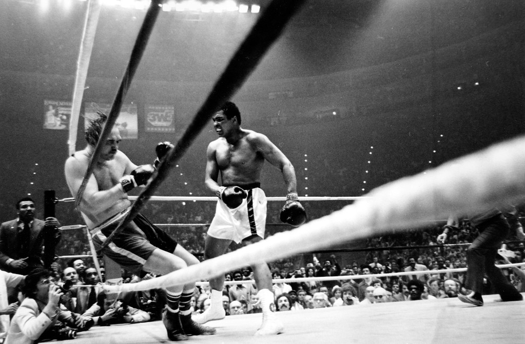 . Chuck Wepner falls to the canvas as heavyweight boxing champion Muhammad Ali stands over him during the 15th round of their title bout at Cleveland Coliseum, Monday night, March 24, 1975.  Ali retained his title with the knockout.  (AP Photo)