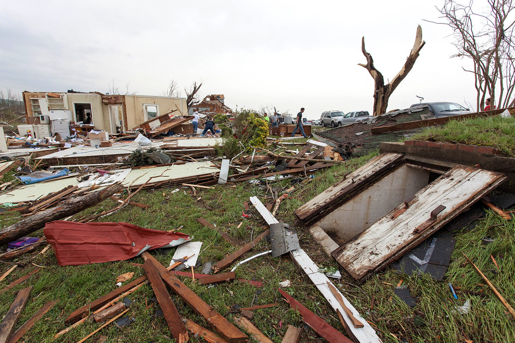 . A storm shelter, right, is where Raella Faulkner and Bobby McElroy and others took shelter in Vilonia, Ark., as a tornado struck the town on Sunday, April 27, 2014. Vilonia was hit hard Sunday after a tornado system ripped through several states in the central U.S. and left more than a dozen dead in a violent start to this year\'s storm season, officials said.  (AP Photo/Karen E. Segrave)