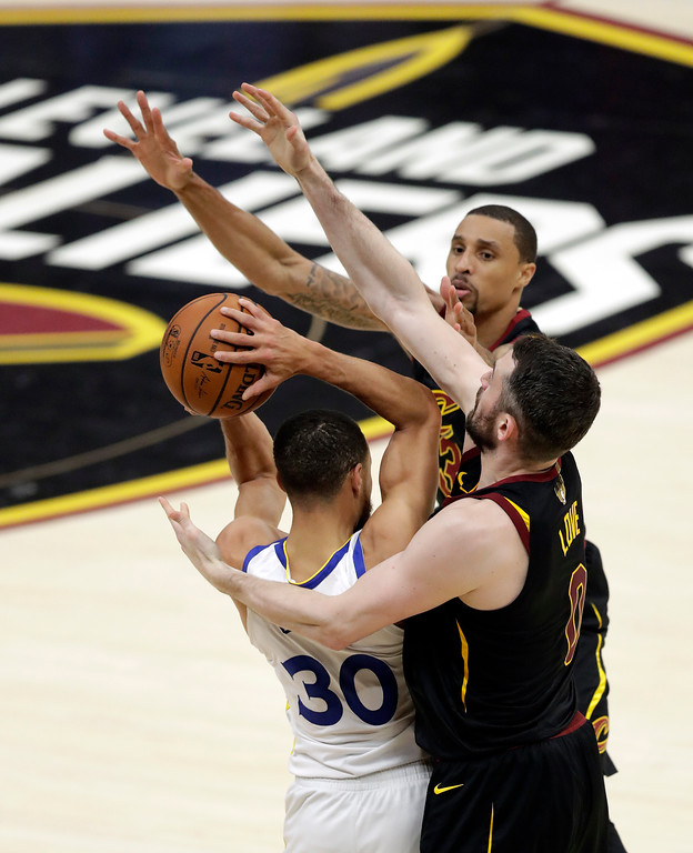 . Golden State Warriors\' Stephen Curry is defended by Cleveland Cavaliers\' George Hill, rear, and Kevin Love during the first half of Game 4 of basketball\'s NBA Finals, Friday, June 8, 2018, in Cleveland. (AP Photo/Tony Dejak)