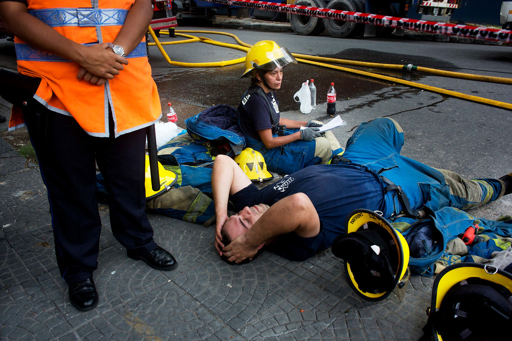 . Firefighters rest after working to extinguish a fire at the Iron Mountain warehouse in Buenos Aires, Argentina, Wednesday, Feb. 5, 2014.  (AP Photo/Rodrigo Abd)