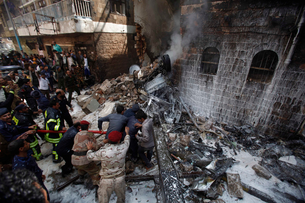 Description of . Military personnel and fire fighters work to extinguish a fire at the site of an aircraft crash in Sanaa February 19, 2013. A Yemeni fighter jet crashed in the centre of the capital Sanaa on Tuesday, killing at least six people, medical sources said. REUTERS/Khaled Abdullah