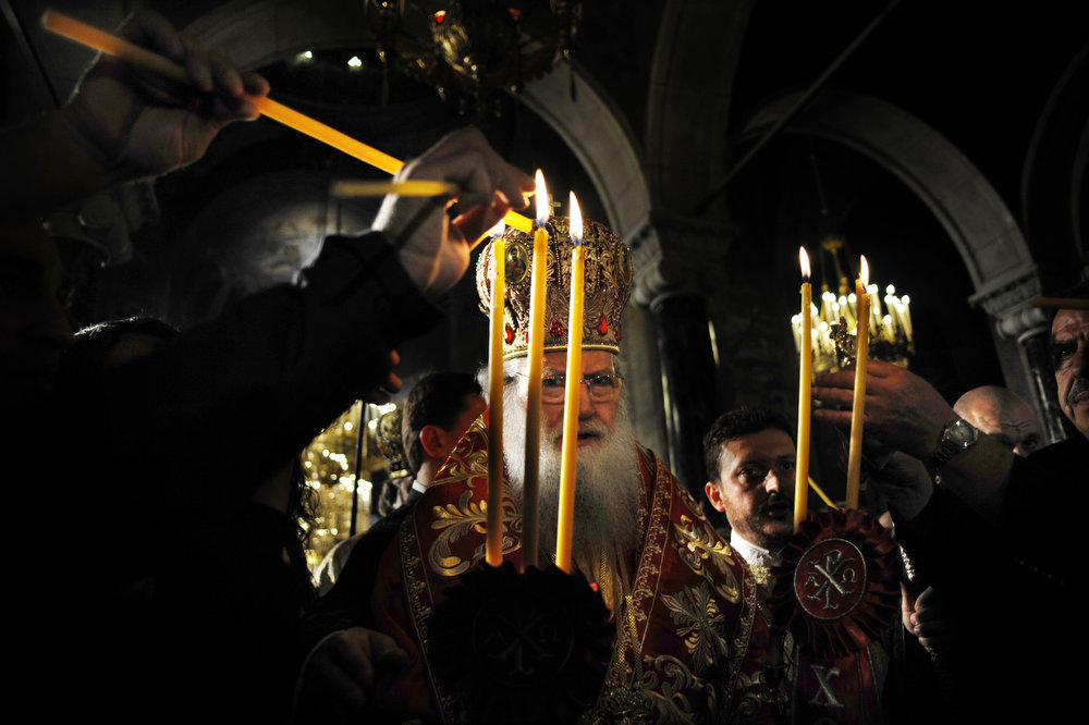 . Bulgaria\'s Orthodox Church newly elected Patriarch Neophyte shares the holy light during the Easter service at the golden-domed Alexander Nevski Cathedral in Sofia on May 5, 2013. The Bulgarian Orthodox Church celebrated Easter, according to the Julian calendar.   NIKOLAY DOYCHINOV/AFP/Getty Images