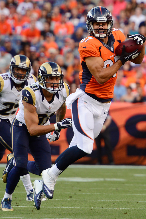 . DENVER, CO - AUGUST 24: Eric Decker (87) of the Denver Broncos makes a first down catch as Cortland Finnegan (31) of the St. Louis Rams pursues during the first half of action of an NFL preseason game at Sports Authority Field at Mile High on August 24, 2013. This is the third game of the preseason for the Broncos. (Photo by AAron Ontiveroz/The Denver Post)