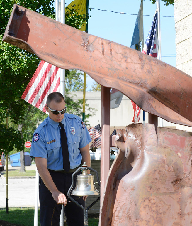 . (News-Herald file) Todd Harvey, an Eastlake firefighter and paramedic, is framed by one of the main support beams from the World Trade Center as he rings the bell in remembrance of Sept. 11 during a ceremony at the Blvd. of 500 Flags in Eastlake, Sept. 7, 2014.