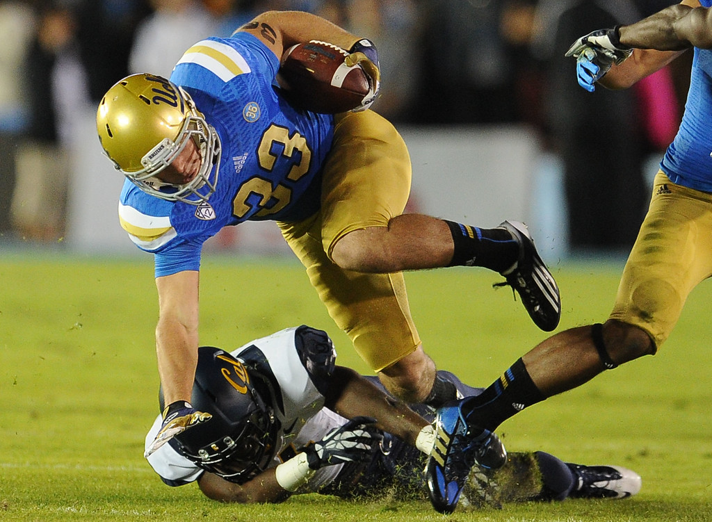 . UCLA running back Steven Manfro (33) runs over a California defender after catching a pass for a 14 yard first down during the first half of their college football game in the Rose Bowl in Pasadena, Calif., on Saturday, Oct. 12, 2013.   (Keith Birmingham Pasadena Star-News)