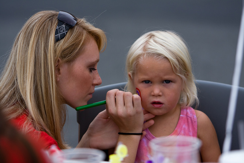 April Wilson of Chi Omega paints a rainbow on the cheek of Ava Bella Gien.