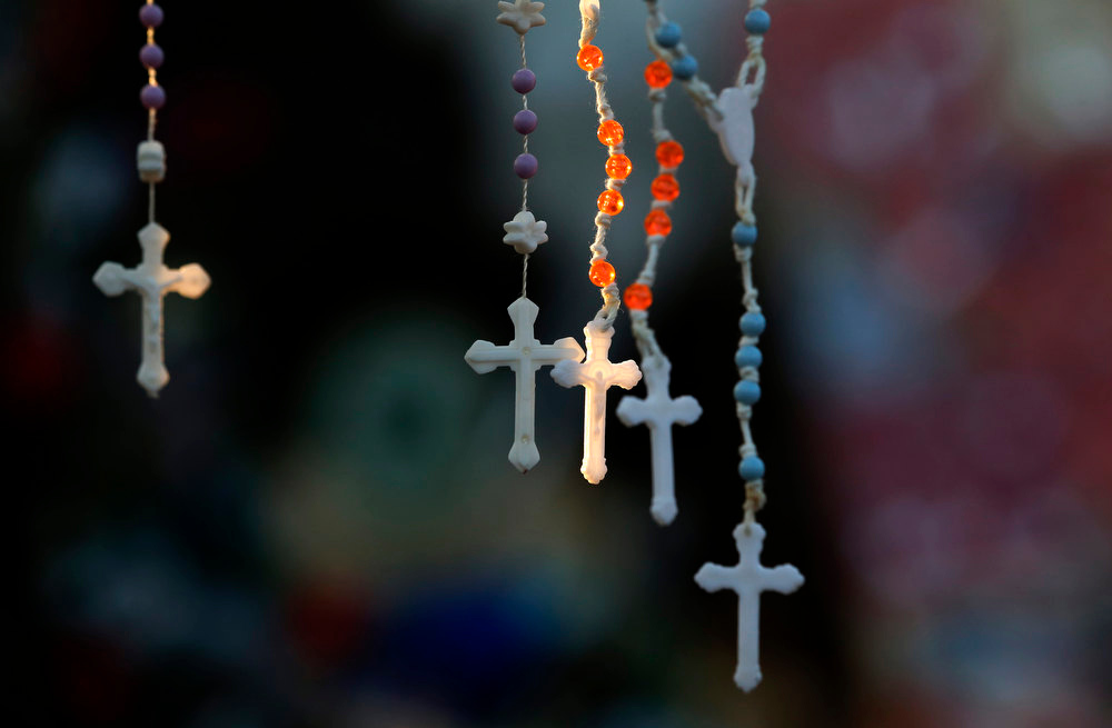 . Rosaries are lit by the morning light on a makeshift memorial near the town Christmas tree in the Sandy Hook village of Newtown, Conn., Wednesday, Dec. 19, 2012. The memorial, which was put up in the aftermath of the elementary school shooting that shocked the small town, is increasing in size as the days go on. More funerals are scheduled for Wednesday, as the town continues to mourn its victims. The gunman, Adam Lanza, walked into Sandy Hook Elementary School in Newtown, Conn., Dec. 14, and opened fire, killing 26 people, including 20 children, before killing himself. (AP Photo/Julio Cortez)