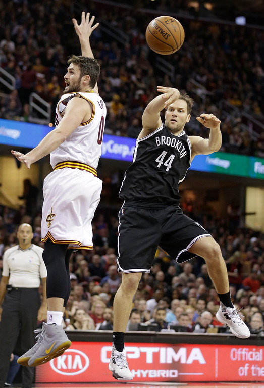 . Brooklyn Nets\' Bojan Bogdanovic (44) passes around Cleveland Cavaliers\' Kevin Love (0) in the first half of an NBA basketball game, Friday, Dec. 23, 2016, in Cleveland. (AP Photo/Tony Dejak)