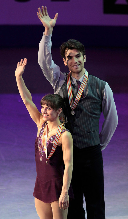 . Meagan Duhamel (L) and Eric Radford of Canada wave during the medal ceremony after placing third at the ISU World Figure Skating Championships in London, March 15, 2013.   REUTERS/Fred Thornhill