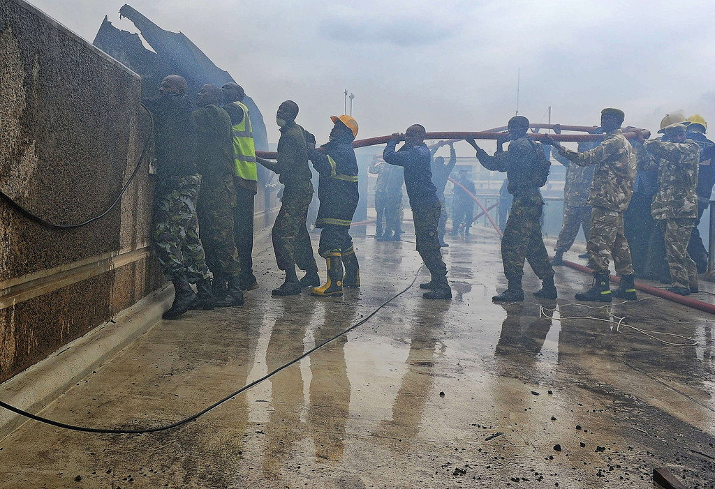. A combined force of fire fighters, military and police spray water canon at the still smoldering terminal at the Jomo Kenyatta International airport in Nairobi on August 7, 2013.   AFP PHOTO / Tony  KARUMBA/AFP/Getty Images